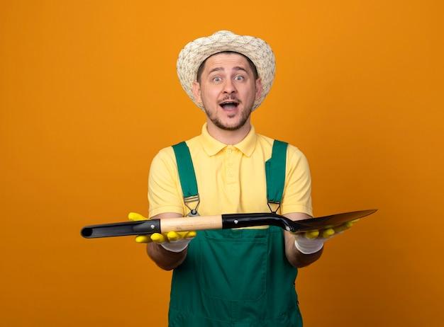 Jovem jardineiro de macacão e chapéu demonstrando uma pá feliz e alegre, sorrindo, olhando para a frente em pé sobre a parede laranja