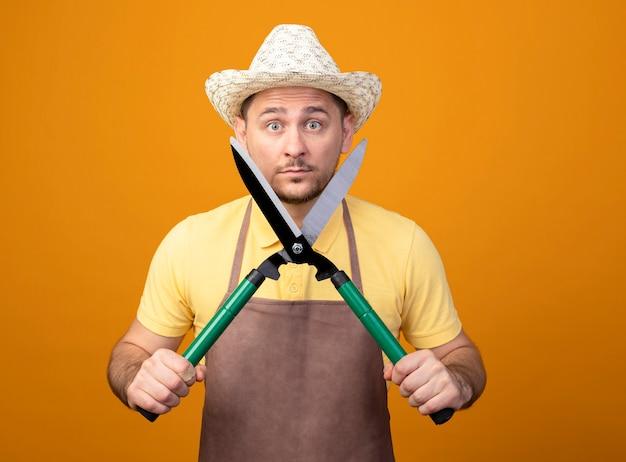 Jovem jardineiro de macacão e chapéu segurando um cortador de cerca viva, olhando para a frente, surpreso e surpreso de pé sobre a parede laranja