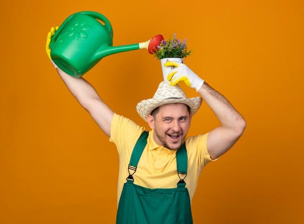 Jovem jardineiro de macacão e chapéu segurando um regador e um vaso de plantas na cabeça, sorrindo alegremente em pé sobre a parede laranja