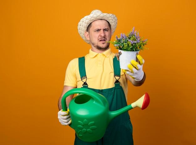 Jovem jardineiro de macacão e chapéu segurando um regador, olhando para um vaso de planta com as duas mãos, ficando descontente e confuso em pé sobre a parede laranja