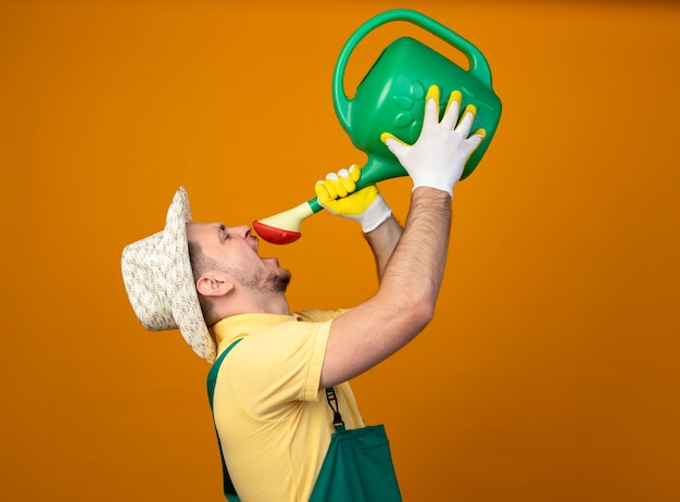 Jovem jardineiro de macacão e chapéu segurando um regador tentando beber água em pé sobre a parede laranja