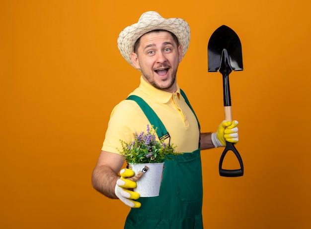 Jovem jardineiro de macacão e chapéu segurando uma pá e mostrando um vaso de plantas sorrindo alegremente
