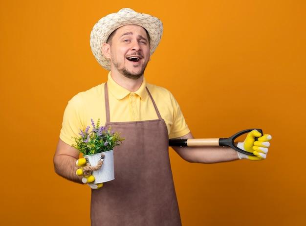 Jovem jardineiro de macacão e chapéu segurando uma pá e um vaso de planta olhando para a frente sorrindo com uma cara feliz em pé sobre a parede laranja