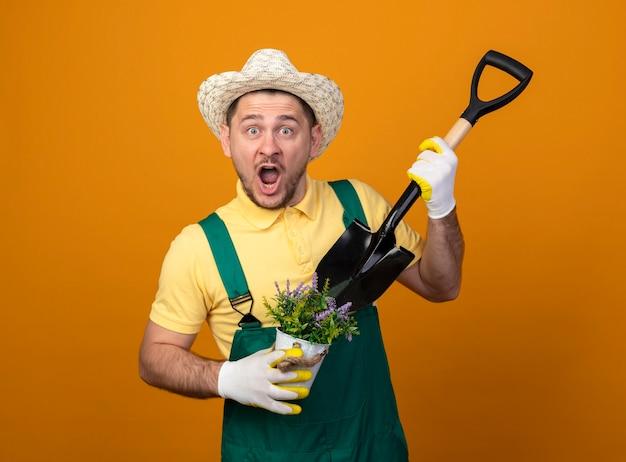 Jovem jardineiro de macacão e chapéu segurando uma pá e um vaso de plantas olhando para a frente surpreso em pé sobre a parede laranja