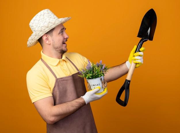 Jovem jardineiro de macacão e chapéu segurando uma pá e um vaso de plantas olhando para a pá com uma cara feliz sorrindo em pé sobre a parede laranja