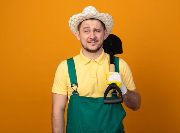 Jovem jardineiro de macacão e chapéu segurando uma pá, olhando para a frente, sorrindo confiante em pé sobre a parede laranja