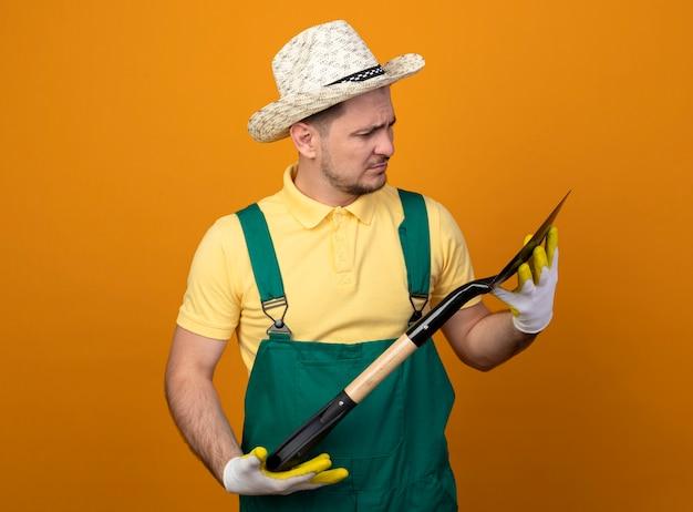 Jovem jardineiro de macacão e chapéu segurando uma pá olhando para ele com cara séria de pé sobre a parede laranja