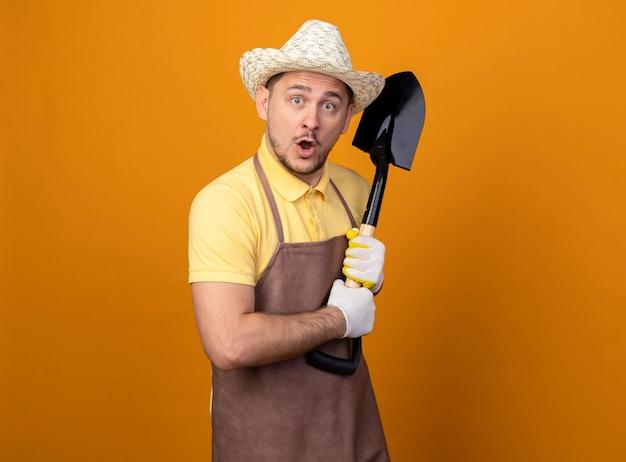 Jovem jardineiro de macacão e chapéu segurando uma pá sendo surpreendido
