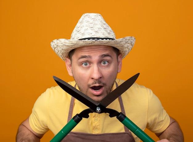 Jovem jardineiro de macacão e chapéu segurando uma tesoura de cerca-viva surpreso e pasmo