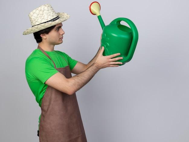 Jovem jardineiro de uniforme com chapéu de jardinagem segurando e olhando para o regador a pensar