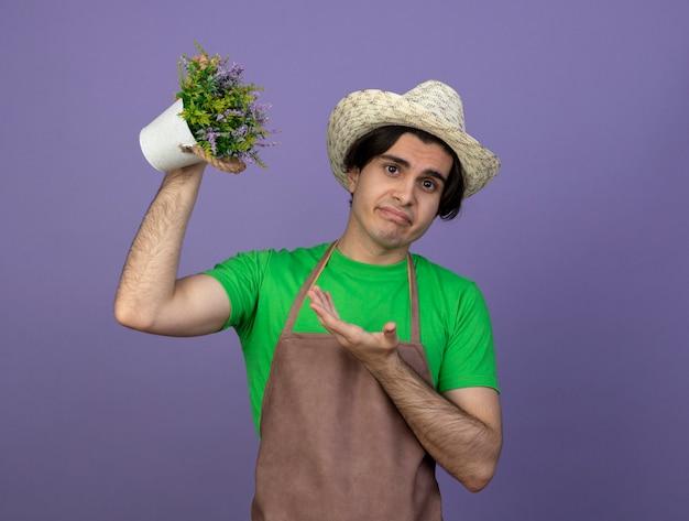 Jovem jardineiro descontente de uniforme usando chapéu de jardinagem levantando e apontando para uma flor em um vaso de flores