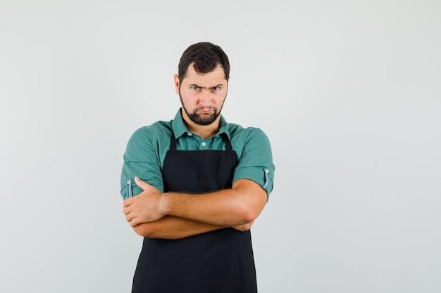Jovem jardineiro em t-shirt, avental em pé com os braços cruzados e olhando ofendido, vista frontal.