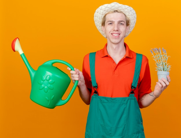 Jovem jardineiro feliz vestindo macacão e chapéu segurando um regador