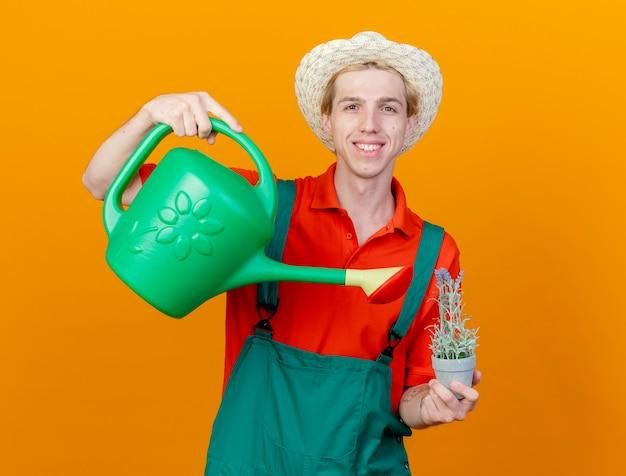 Jovem jardineiro feliz vestindo macacão e chapéu segurando um regador Foto gratuita