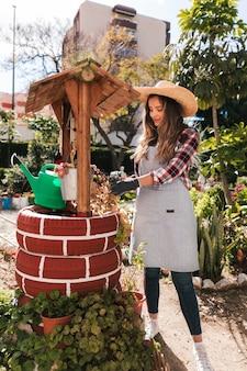 Jovem, jardineiro feminino, cuidando, de, planta, sobre, a, feito à mão, poço