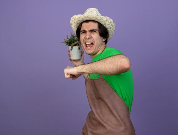 Jovem jardineiro furioso de uniforme, usando chapéu de jardinagem, segurando uma flor em um vaso de flores