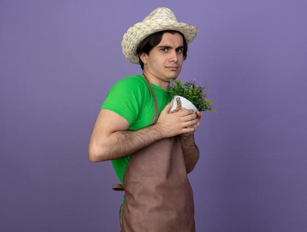 Jovem jardineiro ganancioso de uniforme, usando um chapéu de jardinagem, segurando uma flor em um vaso de flores