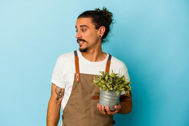 Jovem jardineiro homem caucasiano segurando uma planta isolada em um fundo azul parece de lado sorrindo, alegre e agradável.