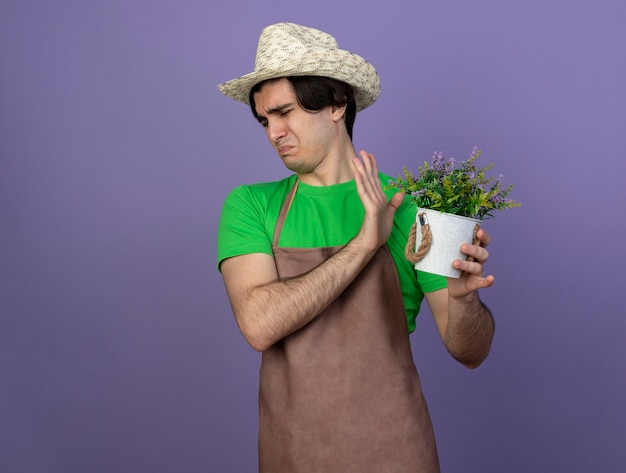 Jovem jardineiro melindroso de uniforme, usando um chapéu de jardinagem, segurando uma flor em um vaso de flores