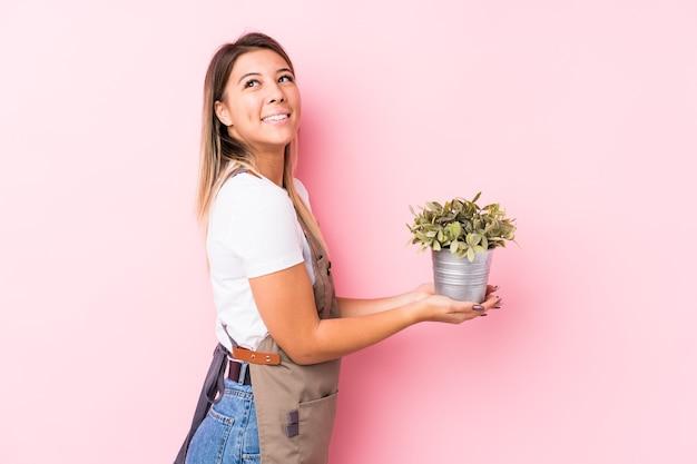 Jovem jardineiro mulher caucasiana isolada parece de lado sorrindo, alegre e agradável.