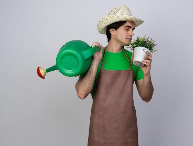 Jovem jardineiro satisfeito de uniforme usando chapéu de jardinagem, colocando um regador no ombro e cheirando uma flor no vaso