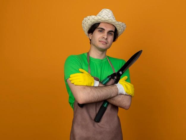 Jovem jardineiro satisfeito em uniforme, usando chapéu de jardinagem e luvas segurando uma tesoura cruzando as mãos isoladas em laranja com espaço de cópia