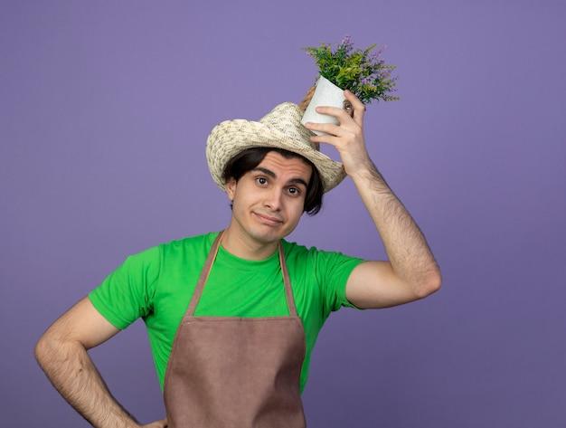Jovem jardineiro satisfeito em uniforme, usando um chapéu de jardinagem, segurando uma flor em um vaso de flores na cabeça