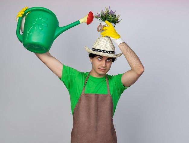 Jovem jardineiro satisfeito, uniformizado, usando chapéu de jardinagem e luvas, regando a flor em um vaso com um regador na cabeça