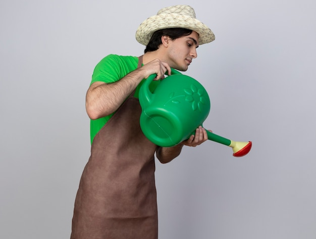 Jovem jardineiro satisfeito, uniformizado, usando chapéu de jardinagem, regando com regador