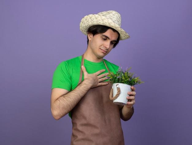 Jovem jardineiro satisfeito, uniformizado, usando chapéu de jardinagem, segurando e olhando para uma flor em um vaso de flores, colocando a mão no peito