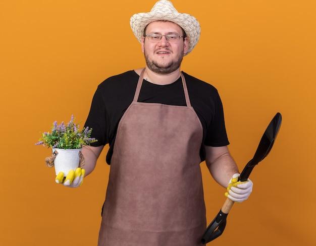 Jovem jardineiro satisfeito usando um chapéu de jardinagem e luvas, segurando uma pá com uma flor em um vaso de flores isolado na parede laranja