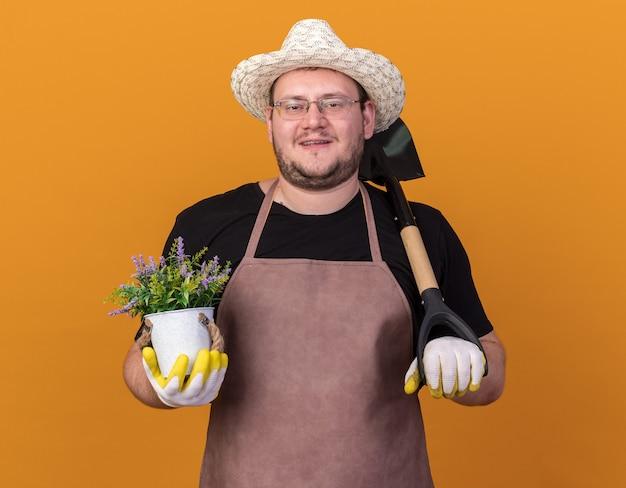 Jovem jardineiro sorridente com chapéu de jardinagem e luvas segurando uma pá com uma flor em um vaso de flores isolado na parede laranja