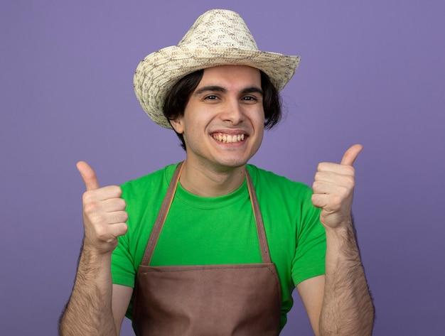 Jovem jardineiro sorridente de uniforme usando chapéu de jardinagem aparecendo os polegares isolados no roxo