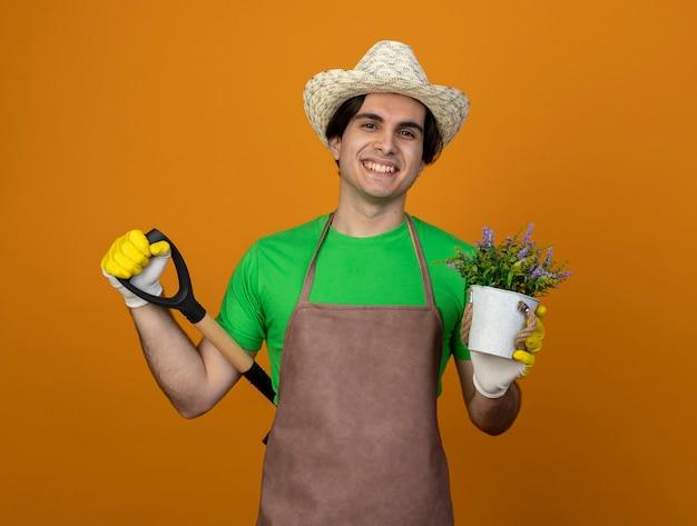 Jovem jardineiro sorridente de uniforme usando chapéu de jardinagem com luvas segurando uma flor em um vaso de flores e colocando a pá na cintura isolada em laranja