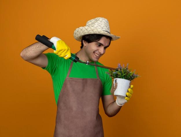 Jovem jardineiro sorridente de uniforme usando chapéu de jardinagem com luvas segurando uma tesoura e uma flor cortada em um vaso de flores