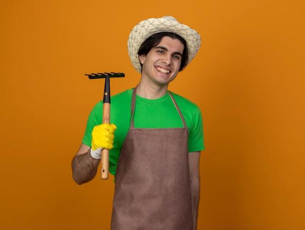 Jovem jardineiro sorridente de uniforme usando chapéu de jardinagem e luvas segurando um ancinho isolado em laranja com espaço de cópia