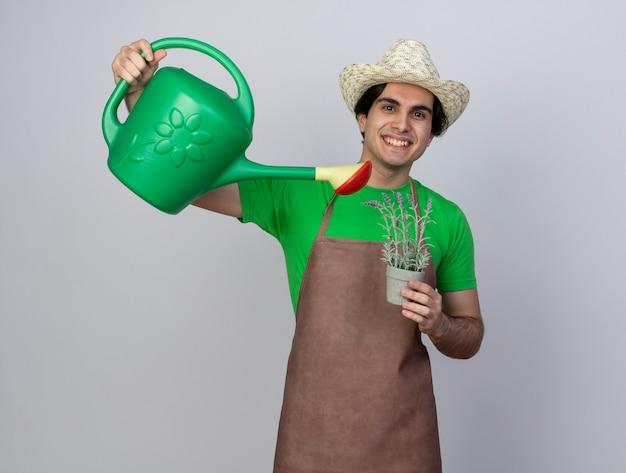 Jovem jardineiro sorridente de uniforme, usando chapéu de jardinagem, regando uma flor em um vaso de flores com um regador