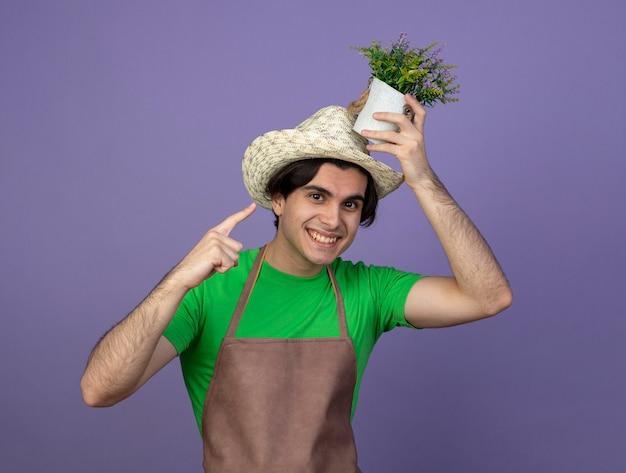 Jovem jardineiro sorridente de uniforme usando chapéu de jardinagem segurando e apontando para uma flor em um vaso de flores na cabeça
