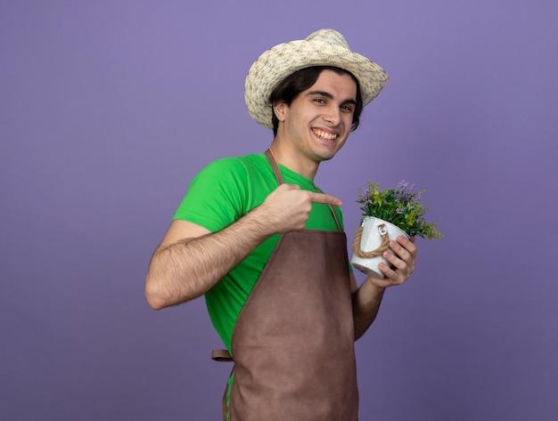 Jovem jardineiro sorridente de uniforme usando chapéu de jardinagem segurando e apontando para uma flor em um vaso de flores