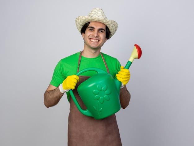 Jovem jardineiro sorridente de uniforme usando chapéu de jardinagem segurando um regador