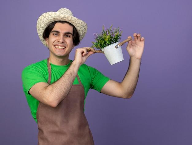 Jovem jardineiro sorridente de uniforme usando chapéu de jardinagem segurando uma flor em um vaso isolado no roxo