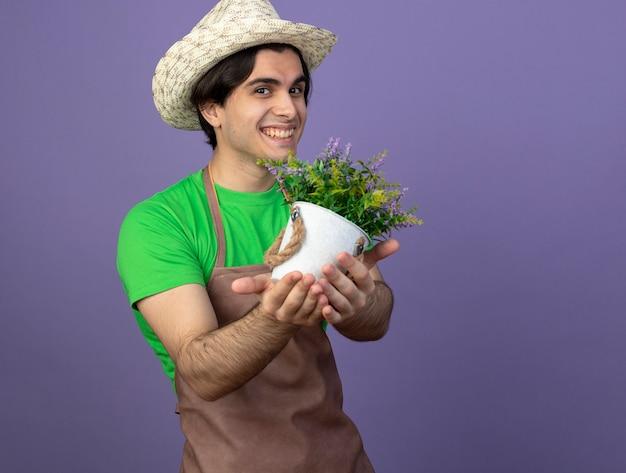 Jovem jardineiro sorridente de uniforme usando chapéu de jardinagem segurando uma flor em um vaso