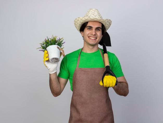 Jovem jardineiro sorridente de uniforme usando luvas e chapéu de jardinagem segurando uma flor em um vaso de flores e colocando a pá no ombro