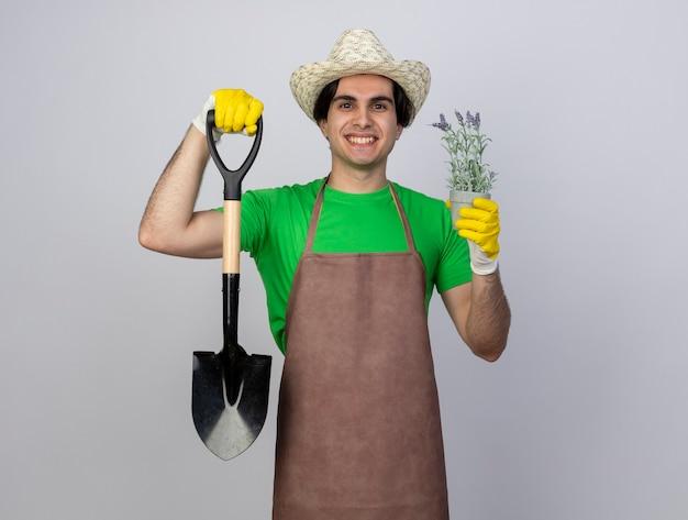 Jovem jardineiro sorridente de uniforme usando luvas e chapéu de jardinagem segurando uma pá com uma flor em um vaso de flores
