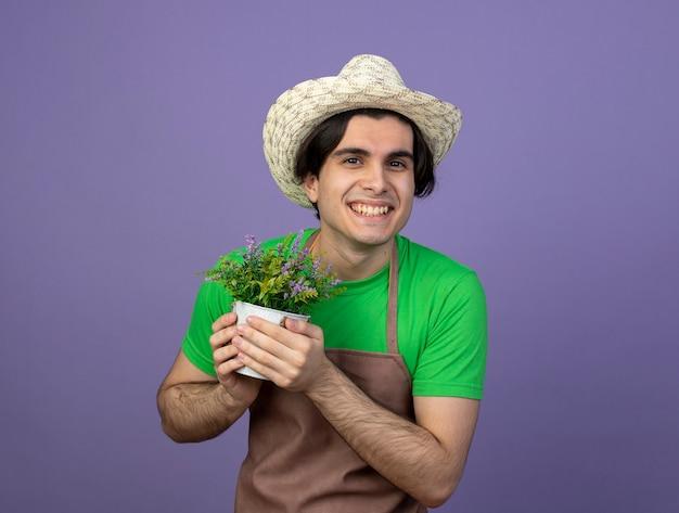 Jovem jardineiro sorridente de uniforme, usando um chapéu de jardinagem, segurando uma flor em um vaso de flores