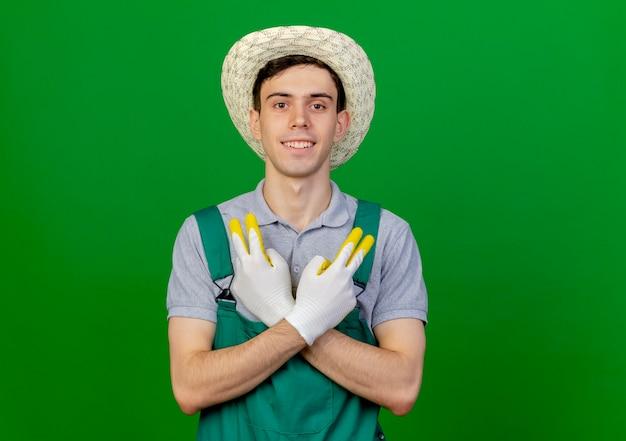 Jovem jardineiro sorridente usando luvas e chapéu de jardinagem gesticula sinal de vitória