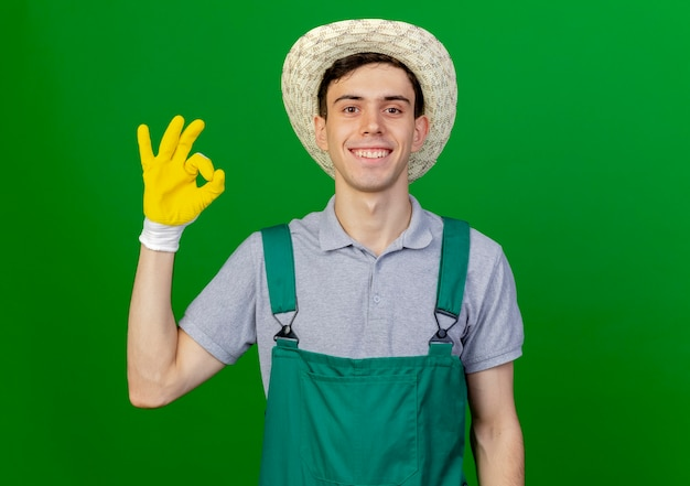 Jovem jardineiro sorridente, usando luvas e chapéu de jardinagem, gestos, mão ok, sinal isolado em um fundo verde com espaço de cópia