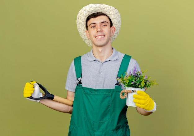 Jovem jardineiro sorridente, usando luvas e chapéu de jardinagem, segurando flores em um vaso de flores e uma pá atrás