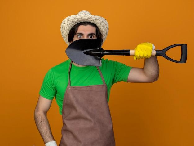 Jovem jardineiro surpreso de uniforme, usando chapéu de jardinagem e luvas, rosto coberto com pá isolada em laranja
