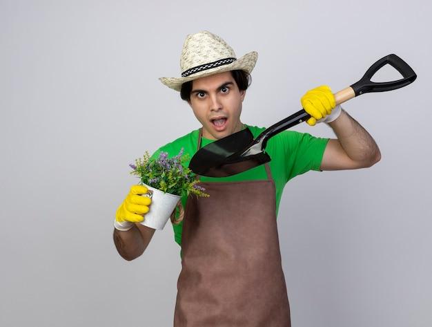 Jovem jardineiro surpreso de uniforme usando chapéu de jardinagem e luvas segurando e apontando para uma flor em um vaso de flores com uma pá
